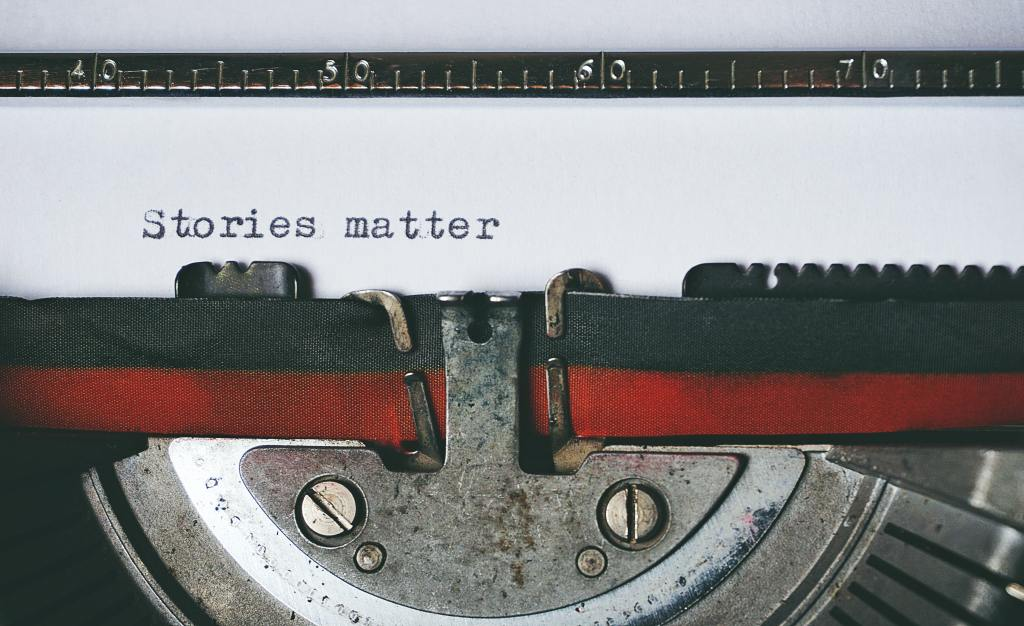 """Image of author typing """"Stories matter"""""""